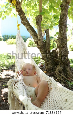 An adorable baby boy sleeps outside in a hammock while dreaming sweetly. - stock photo