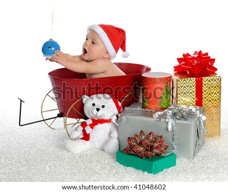 An adorable baby boy surrounded by Christmas gifts, attempting to get at a hanging Christmas bulb.  Isolated on white.