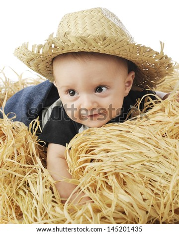 An adorable baby boy wearing a straw hat as he happily lays on a stack of hay.  - stock photo