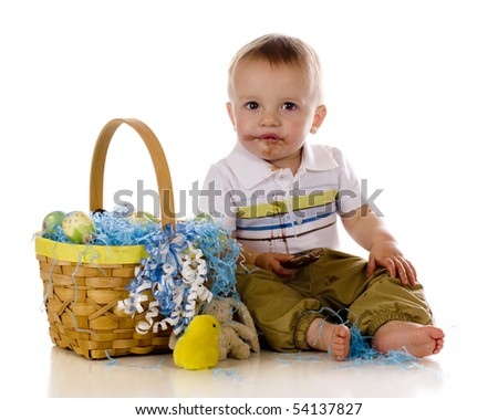 An adorable baby eating chocolate from his Easter basket.  Isolated on white. - stock photo