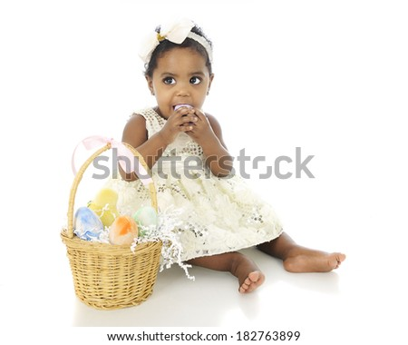An adorable baby girl all dressed up with an Easter basket by her side.  She's attempting to eat one of the colored eggs.  On a white background, - stock photo