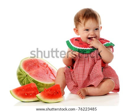 An adorable baby girl delighted with her first taste of watermelon.  Isolated on white. - stock photo