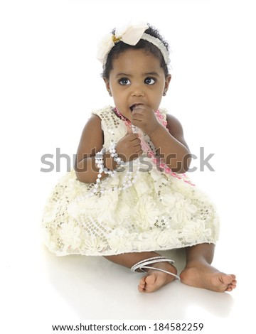 An adorable baby girl, dressed up in a white hair bow, dress and jewelery.  She's tasting the pink necklace that she wears.  On a white background. - stock photo