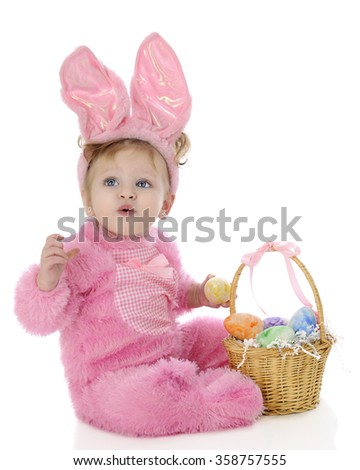 """An adorable baby girl """"Easter bunny"""" attempting to whistle as she sits by her basket filled with colorful eggs.  On a white background. - stock photo"""