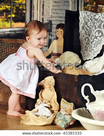 An adorable baby girl happily exploring the things in Grandma's trunk. - stock photo