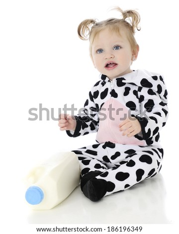 An adorable baby girl happy in her holstein cow costume, sitting by a bottle of milk.  On a white background. - stock photo