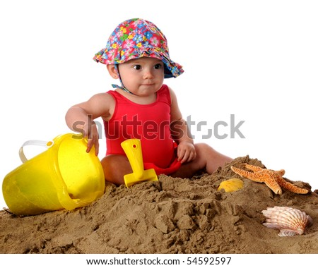 An adorable baby girl in a bathing suit and sunhat playing in the sand.  Isolated on white. - stock photo