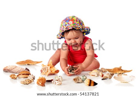 An adorable baby girl in her swimsuit and sunhat examining one of several seashells.  Isolated on white. - stock photo
