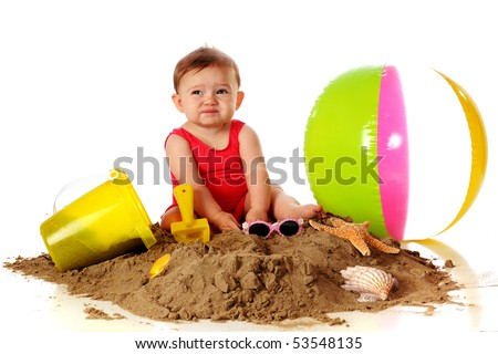 """An adorable baby girl making a """"Yuck"""" face while playing in the sand with beach toys. - stock photo"""