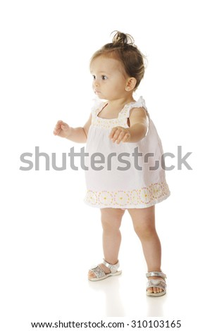 An adorable baby girl nervously taking her first steps.  On a white background.