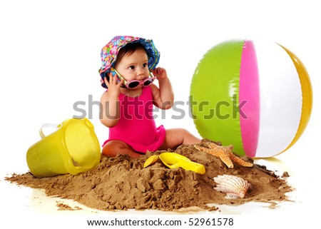 An adorable baby girl trying on sunglasses as she plays in a pile of sand with beach toys and shells.  Isolated on white. - stock photo
