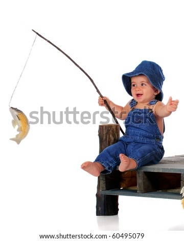 An adorable baby in overalls happily pulls up a fish on his line.  Isolated on white. - stock photo