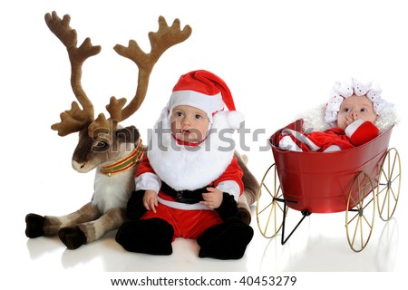 An adorable baby santa with his reindeer with baby Mrs. Claus in a wagon nearby.  Isolated on white. - stock photo