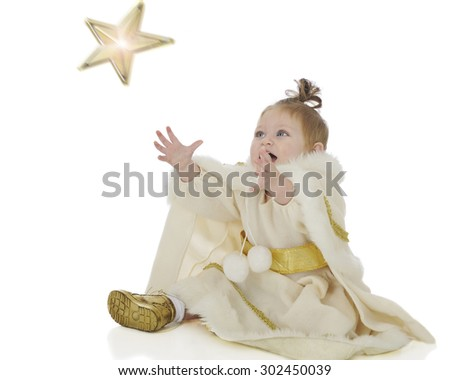 "An adorable baby ""snow princes"" delightedly reaching up to catch a falling star.  Motion blur on the star.  On a white background. - stock photo"