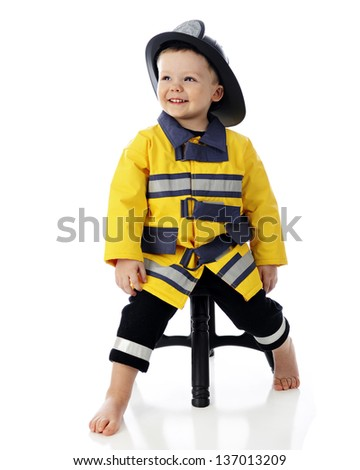 An adorable, barefoot toddler happily leaning on a stool in his fireman outfit.  On a white background. - stock photo