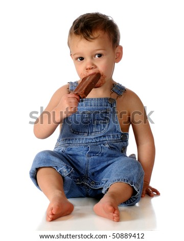 An adorable, barefoot toddler in overalls enjoying a chocolate frozen bar.  Isolated on white. - stock photo