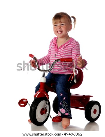 An adorable, barefoot two-year-old sitting on a little ried tricycle.  Isolated on white. - stock photo