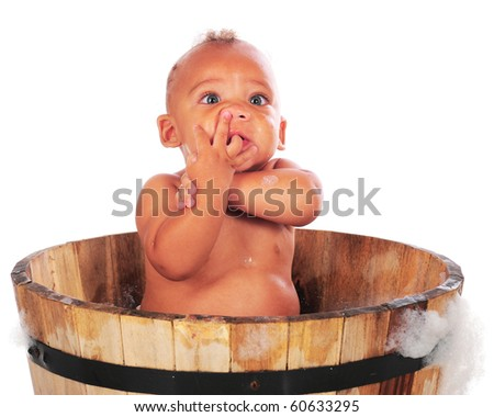 An adorable biracial baby bathing in a wooden tub with his arms twisted, his fingers curled into his mouth and under his nose.  Isolated on white.