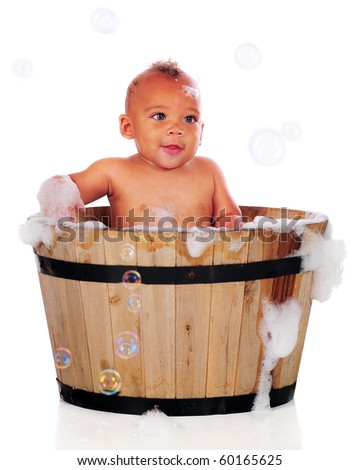 An adorable biracial baby bathing with bubbles in an old wooden tub.  Isolated on white.