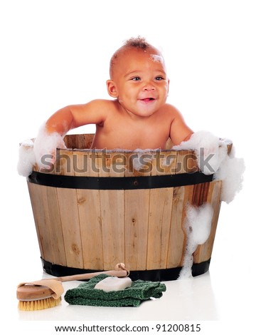 An adorable biracial baby happily taking a bath in an old wooden tub.  On a white background. - stock photo