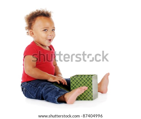 An adorable biracial baby looking up with pleasing surprise while opening his gift box.  On a white background.
