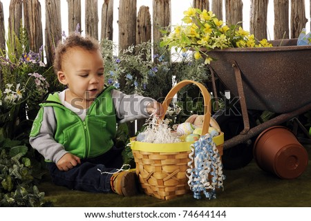 An adorable biracial baby playing in his Easter basket in a flower garden.