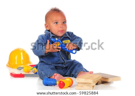 An adorable biracial baby workman overalls, surrounded by colorful toy tools , a hard hat and rough wood blocks.  Isolated on white.