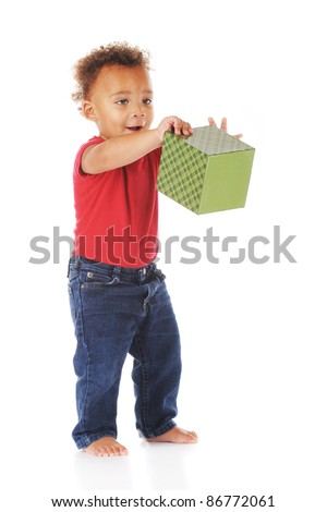 An adorable biracial toddler happily dumping a gift-wrapped box.  On a white background. - stock photo
