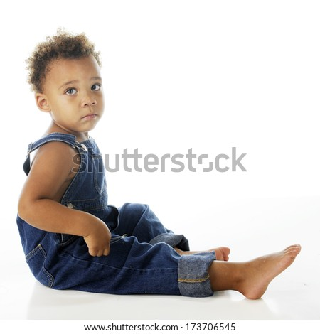 An adorable, but sad, biracial tot dressed only in denim overalls.  On a white background.