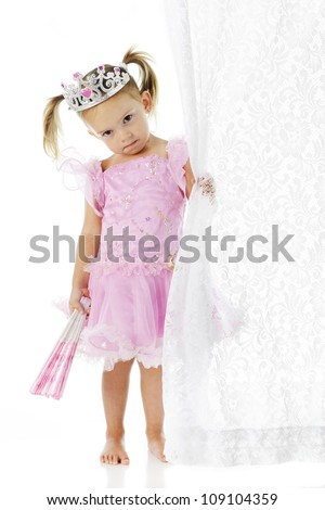 An adorable but sad preschool princess clutching a closed fan in one hand and a lacy curtain in the other.  On a white background. - stock photo