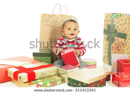 An adorable, dressed up baby boy enjoying the wrapped gifts that surround him.  On a white background. - stock photo
