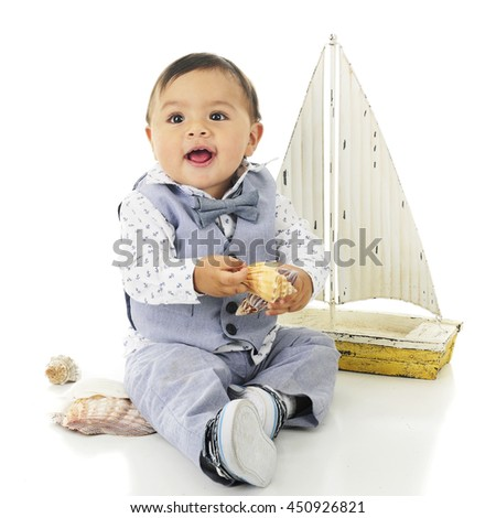 An adorable, dressed up baby boy looking up happily as he hold two beautiful sea shells.  On a white background. - stock photo