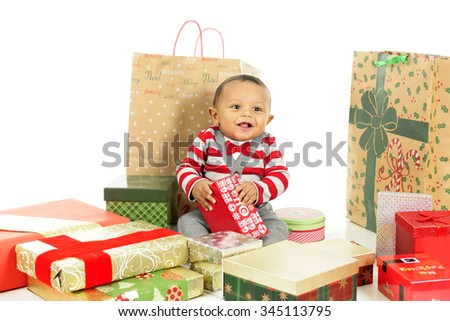 An adorable, dressed up baby boy obviously loving being surrounded by lots of wrapped gifts.  On a white background. - stock photo