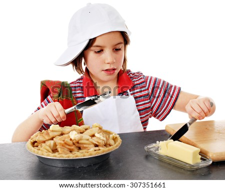 An adorable elementary baker slicing butter to put on the apple slices she has in her pie shell.  On a white background. - stock photo