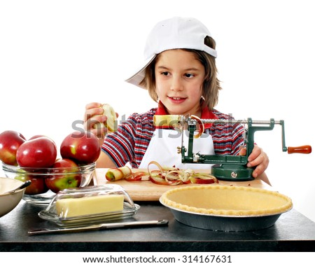 """An adorable elementary """"baker"""" using an apple peeler as she begins making an apple pie.  On a white background. - stock photo"""