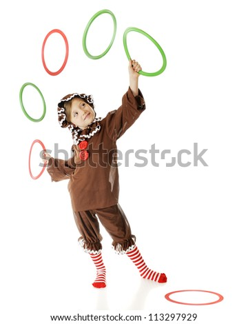 "An adorable elementary ""gingerbread girl"" happily juggling Christmas colored rings.  (Motion blur on airborne rings.)  On a white background."