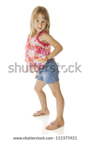 An adorable elementary girl getting sassy in her frilly top and denim shorts.  On a white background.