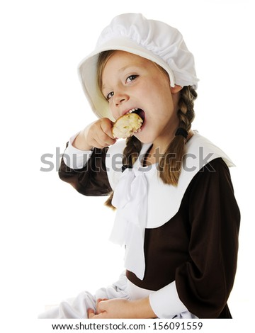 An adorable elementary Pilgrim girl happily biting a chicken drumstick.  On a white background.