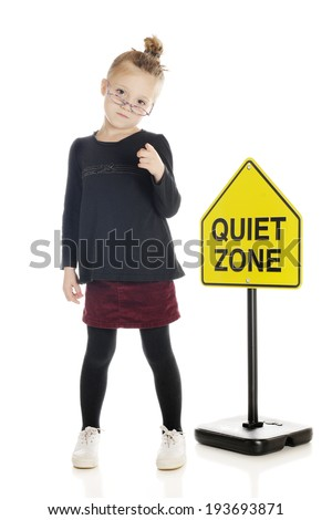 """An adorable elementary """"teacher/librarian"""" sternly pointing her finger at the viewer in front of a """"quiet zone"""" sign.  On a white background. - stock photo"""