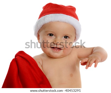 An adorable, happy baby boy dressed only in a Santa hat, holding up his red suit to get ready for his big Christmas Eve ride. - stock photo