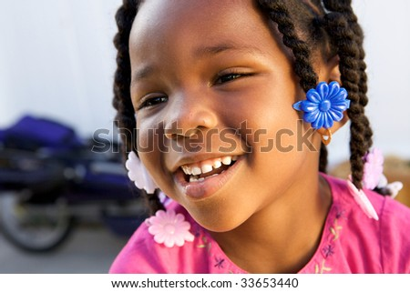 An adorable little african american girl in a pink shirt - stock photo