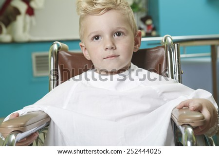 An adorable little boy in the wheelchair at the hospital - stock photo