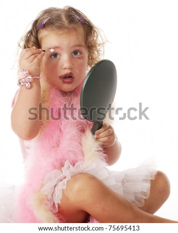 An adorable little girl in boas and petticoat, looking up from applying mommy's makeup on herself. - stock photo