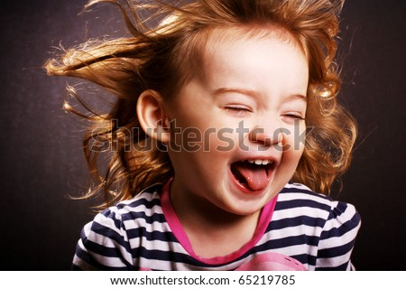 An adorable little girl laughing with wind in her hair. - stock photo