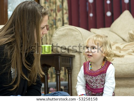 An adorable little girl listening to a young woman telling a story