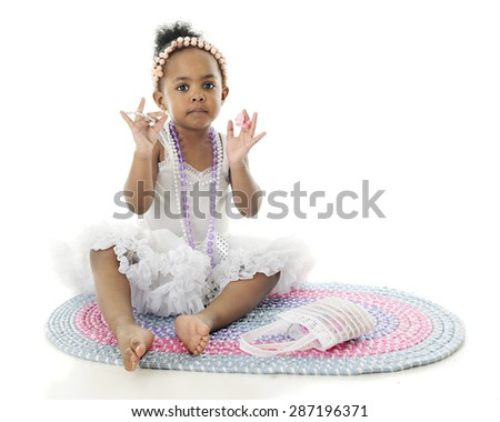 An adorable little girl sitting on a rug in her white petticoat.  She's adorned with strands of beads and holds up a bracelet and rings.  On a white background with space on the right for your text. - stock photo