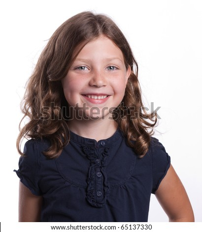 An adorable little girl with curly hair, blue eyes, and freckles looking happy and smiling - stock photo