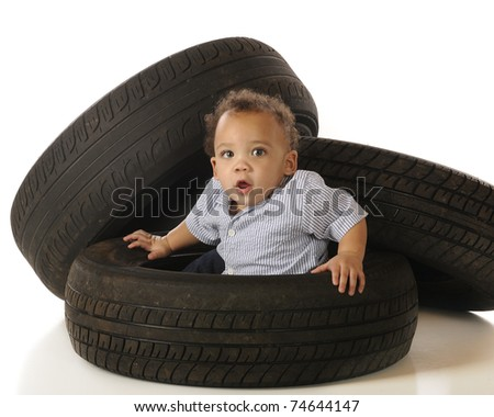 An adorable mixed-race baby pulling himself up out of an old tire.  Isolated on white. - stock photo