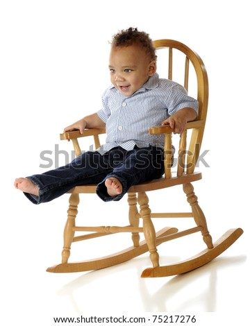 An adorable mixed-race toddler enjoying a child-size rocker.  Isolated on white.