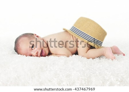 An adorable newborn smiling at the viewer as he lays on his belly on a fluffy white blanket with a straw fedora style hat on his behind.  On a white background. - stock photo